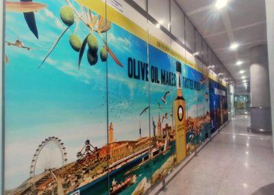 Impresión de vinilos y montaje para la campaña publicitaria de aceite de oliva en el Aeropuerto de Málaga.